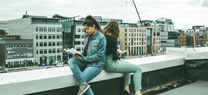 To jenter leser. De sitter ute på et tak. Utsikt mot Moloveien i Bodø.
