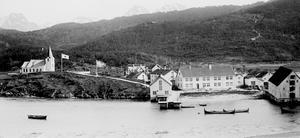 Svart-hvit bilde av fiskevær med kirke, brygge og hus