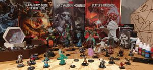 Dungeons & Dragons figurer, og bøker i bakgrunn.